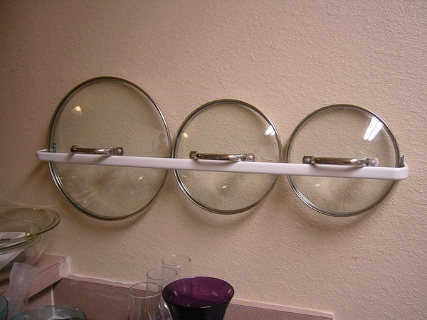 Hang a long towel bar to store pot lids and other hangable items