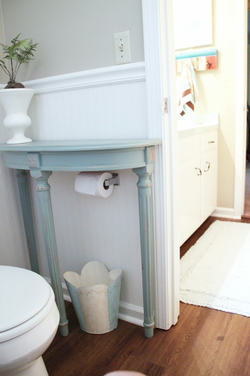 Add a half table over a toilet paper holder for extra storage