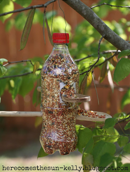 Make a bird feeder using a recycled soda bottle and two wooden spoons