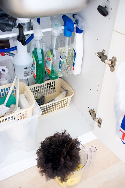 Use a tension rod to hang spray bottles in your undersink cabinet