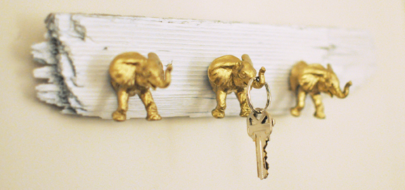 Use plastic toys, gold spray paint, and driftwood to make these cute key hooks